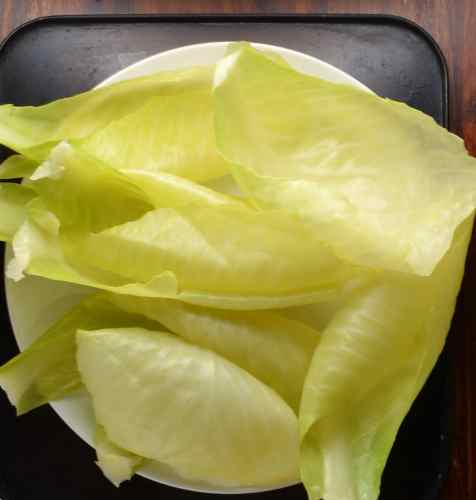 Cooked loose cabbage leaves on white plate on dark surface.
