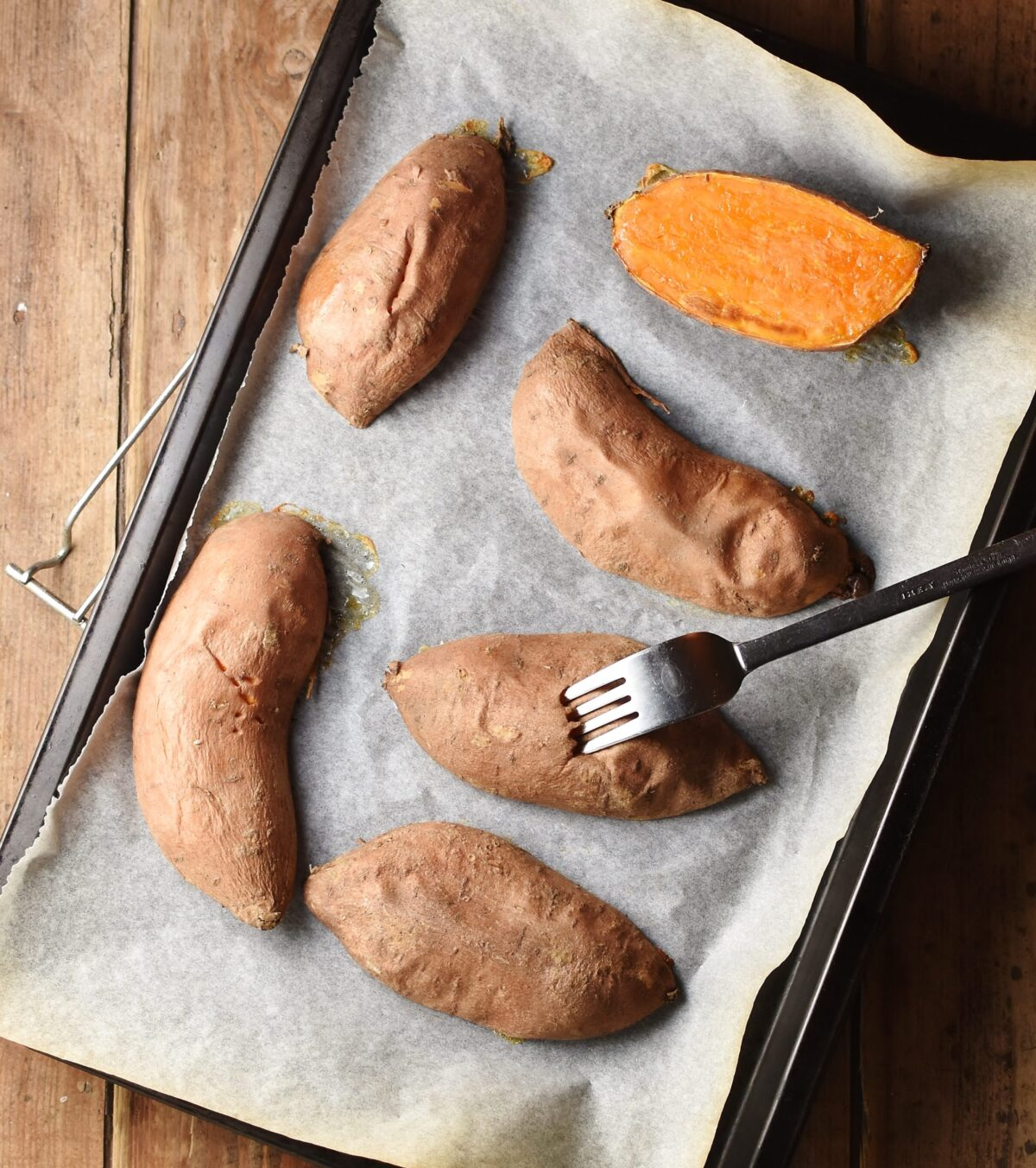 Sweet potato halves with fork on top of baking sheet lined with paper.