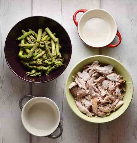 Top down view of chopped asparagus and chicken in separate bowls, and 2 ramekins.