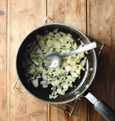 Chopped onions in large pot with spoon.