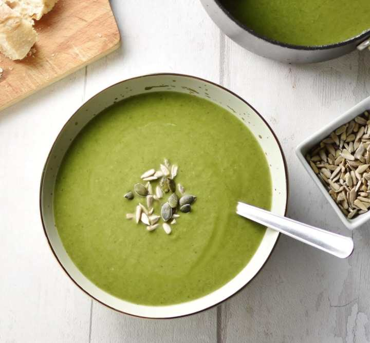 Top down view of broccoli spinach soup with seeds in grey bowl with spoon, seeds and saucepan with soup to right and wooden board in top left corner.