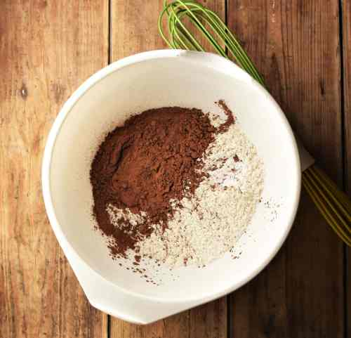 Flour and cocoa powder in large white bowl with green whisk.