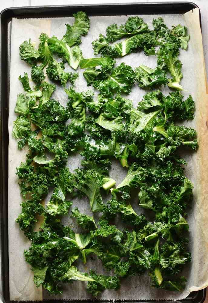 Top down view of kale leaves on top of parchment paper.