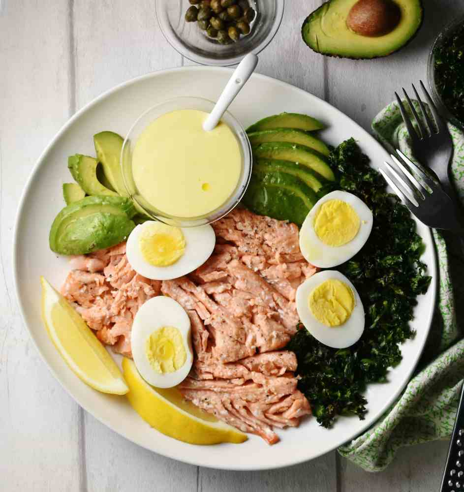 Top down view of salmon, avocado slices, egg halves, lemon wedges, crispy kale and dressing in small dish on top of white plate, with 2 forks on top of green cloth to right.