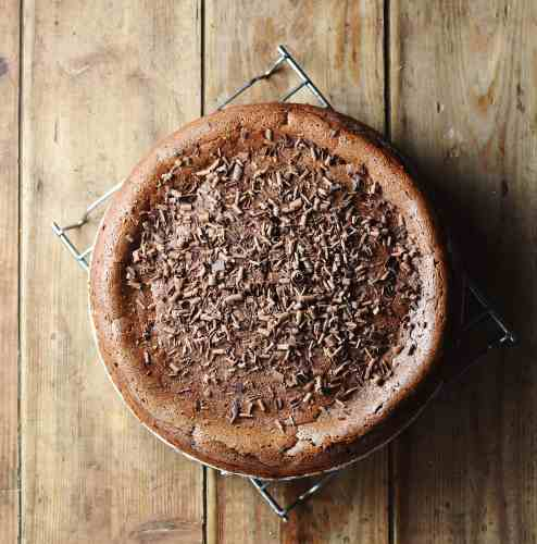 Baked chocolate cheesecake with chocolate shavings on top of cooling rack.