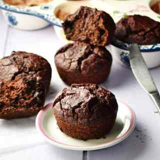 Side view of beetroot chocolate muffins on top of small white plate and inside ceramic muffin pan, with knife in background.