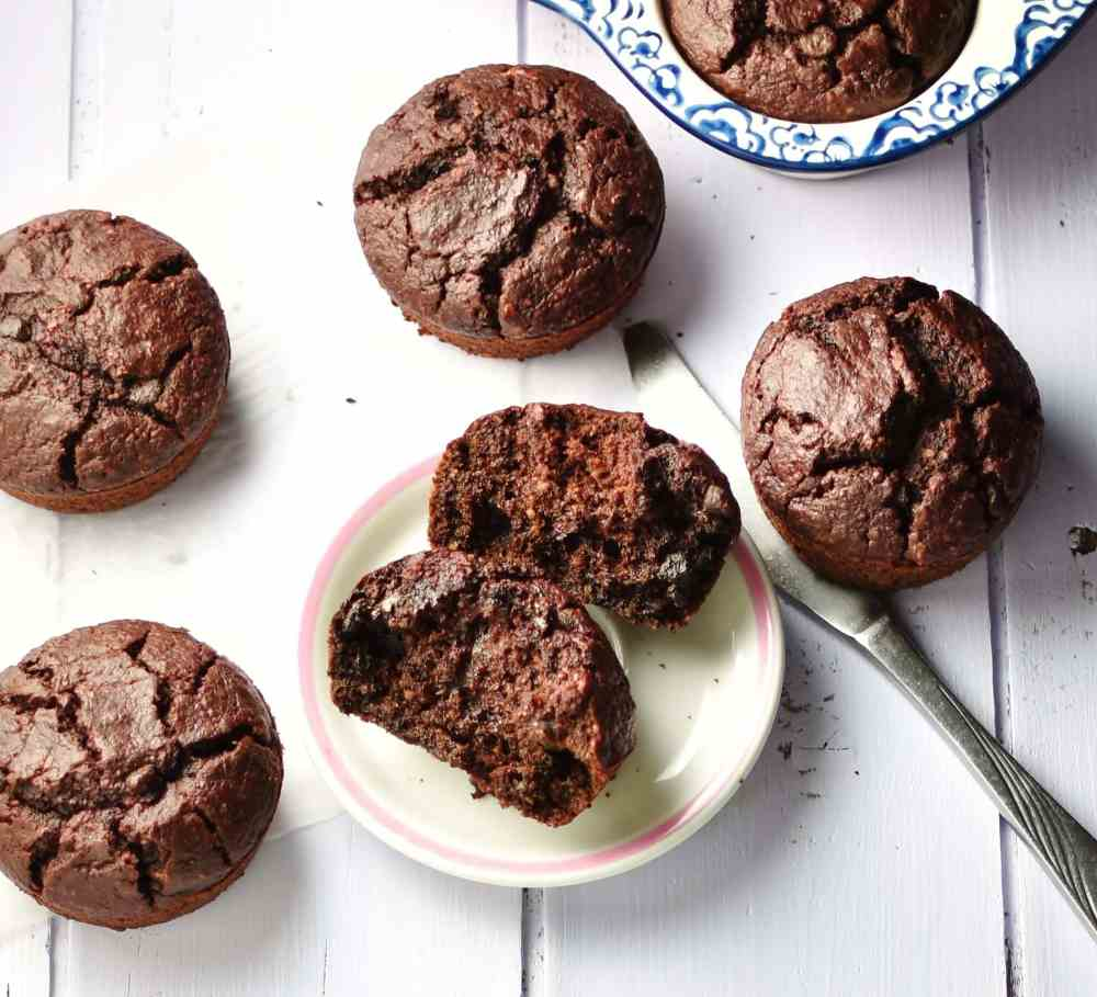Top down view of chocolate muffins on top of small white plate, paper and inside ceramic muffin pan in background.