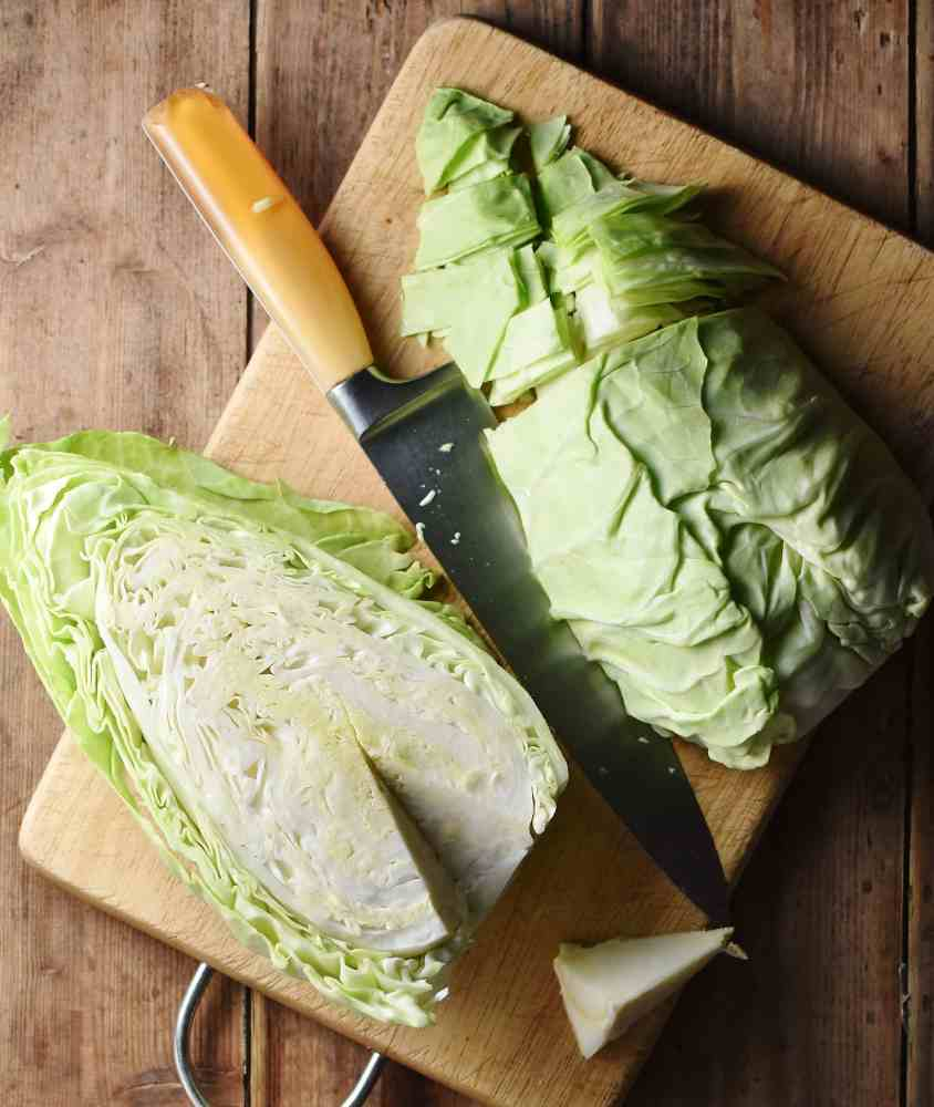 2 halves of pointed cabbage, partly chopped on cutting board with knife.