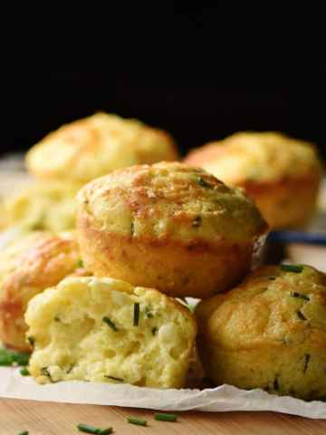 Side view of cauliflower muffins on top of baking paper.