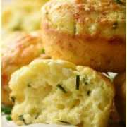 Close-up side view of cauliflower muffins with chives on top of baking paper.