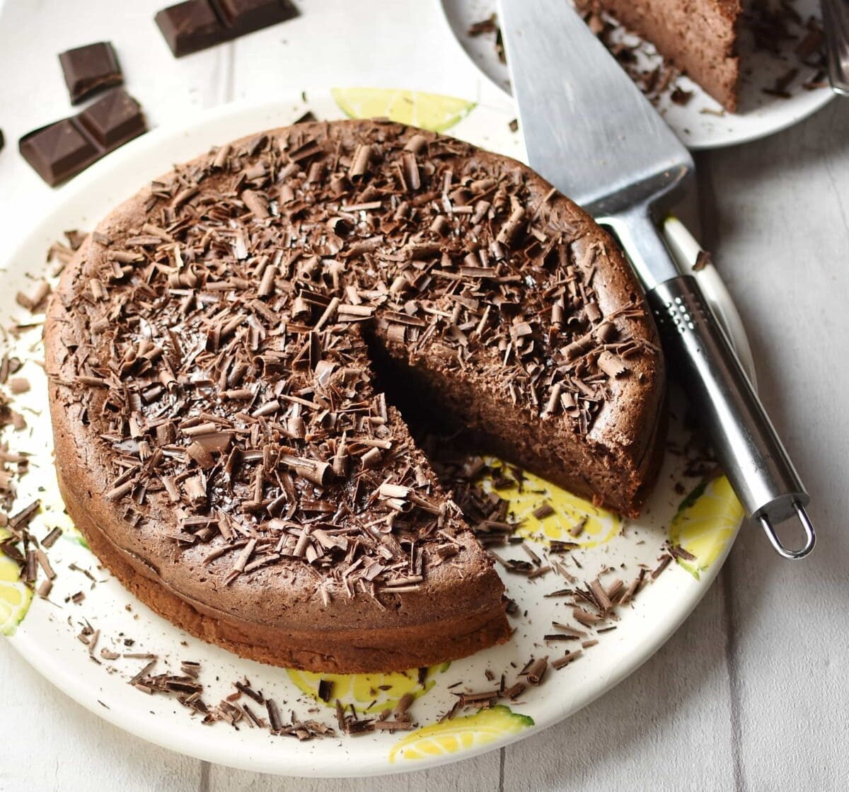 Chocolate ricotta cheesecake with chocolate shavings and metal spatula on top of white plate with yellow pattern, and chocolate pieces and partial view of cake in background.