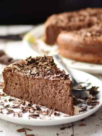 Chocolate cheesecake slice with chocolate shavings and spoon on top of white plate, with cheesecake in background.