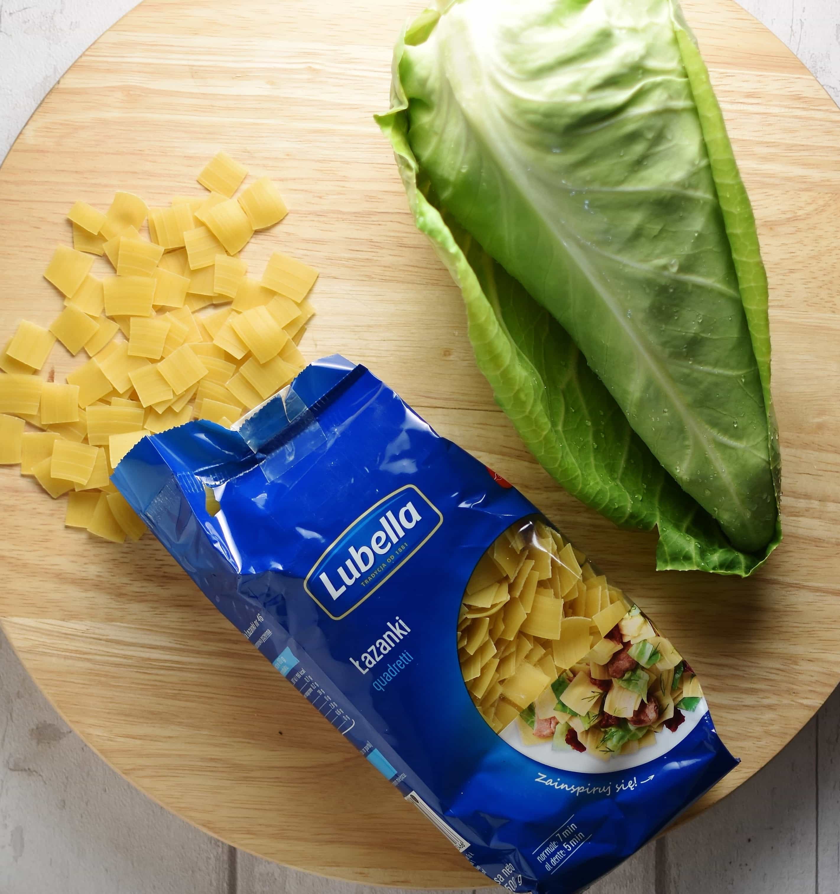 Top down view of Polish lazanki pasta in package, with pointed cabbage on top of round wooden board.
