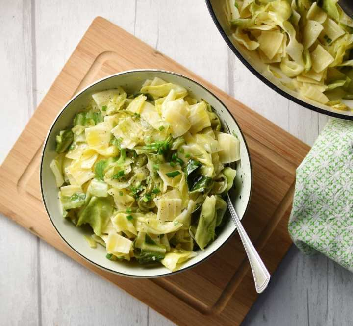 Top down view of Polish pasta with cabbage in bowl with spoon on top of wooden board, with partial view of pasta in white dish in top right corner.