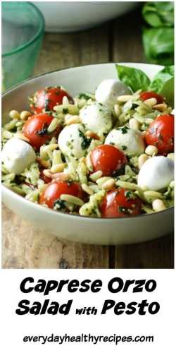 Close-up partial view of orzo pesto salad with cherry tomatoes and mozzarella balls inside light green bowl.