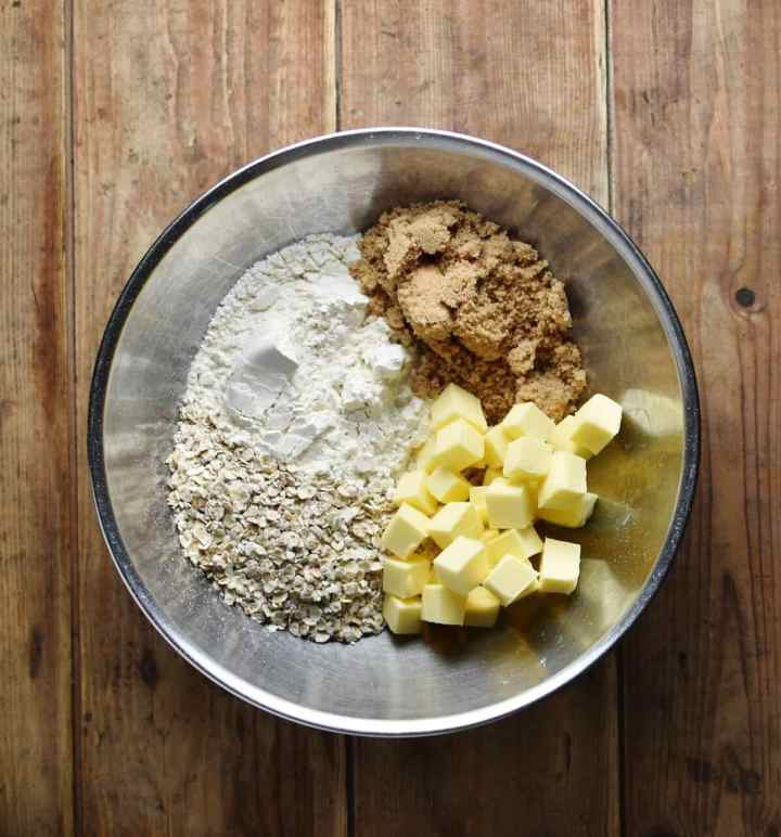 Top down view of oats, flour, sugar and cubed butter in metal bowl.