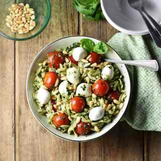 Top down view of orzo salad with pesto, cherry tomatoes, mini mozzarellas and spoon in white bowl wrapped in green cloth, with white bowl in top right and pine nuts in small dish in top left corner.