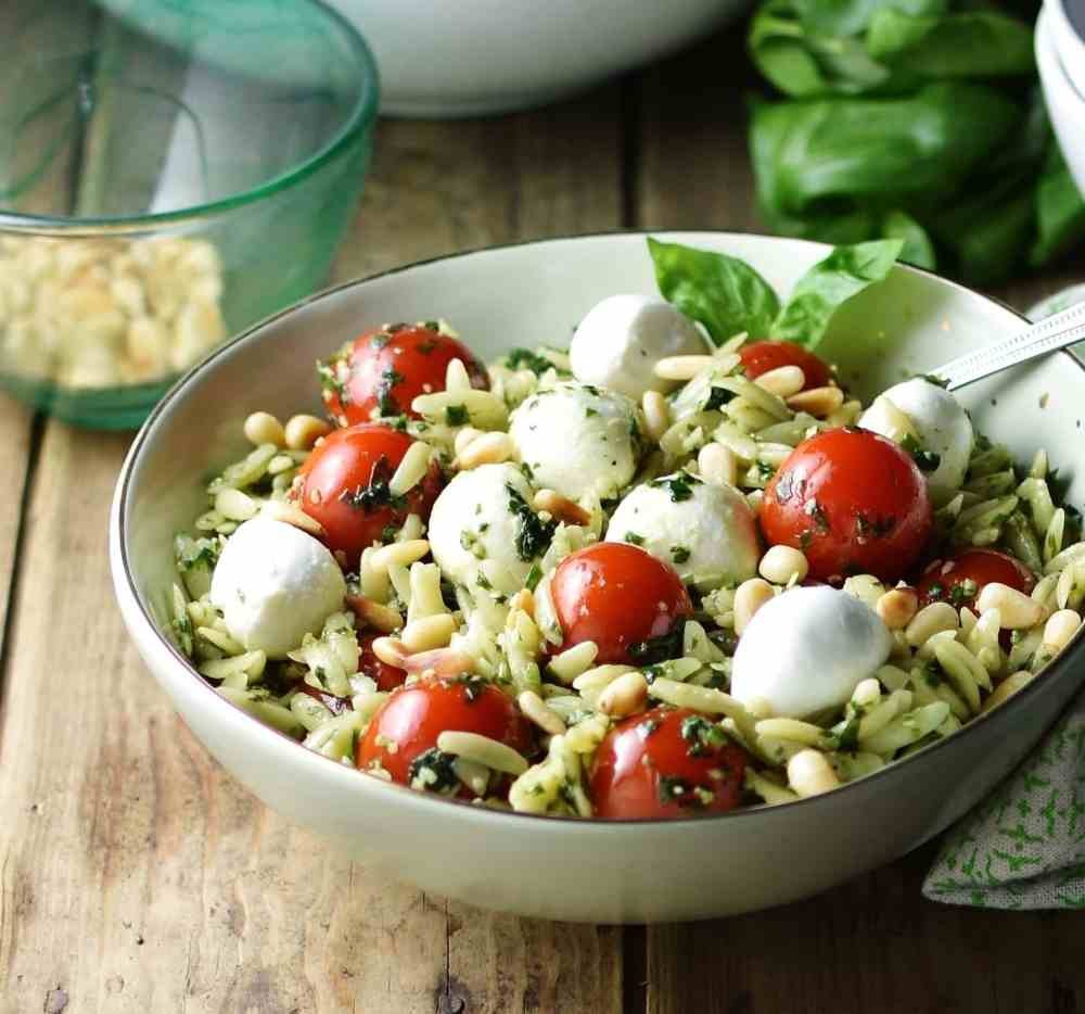 Close-up side view of pasta salad with cherry tomatoes and mini mozzarellas inside light green bowl, with basil leaves, pine nuts in small dish and large white bowl in background.