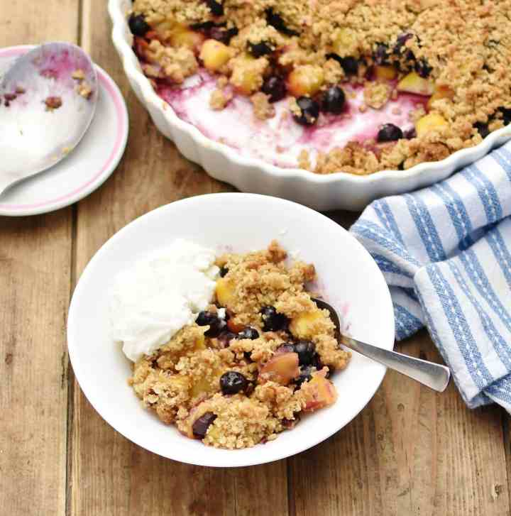 Blueberry peach crumble with yogurt and spoon inside white bowl, with partial view of white casserole dish containing crumble, wrapped in blue-and-white stripy cloth, and large spoon on top of saucer in background.