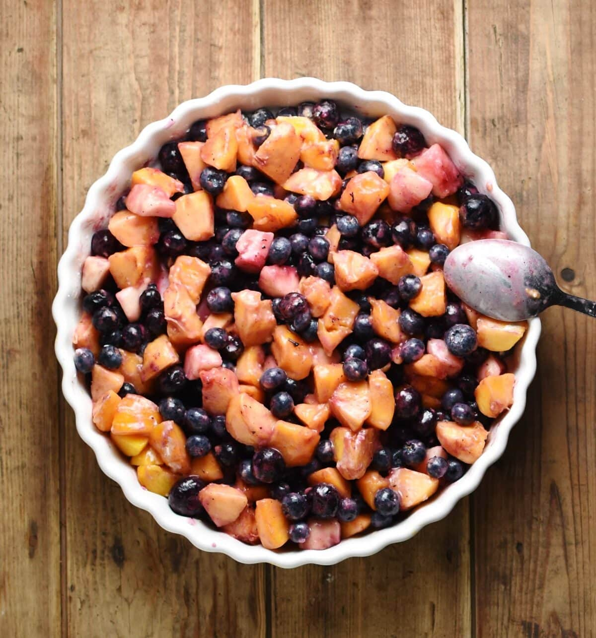 Top down view of cubed peaches and blueberries inside white round dish with spoon to the right.