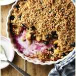 Top down view of peach and blueberry crumble inside white round ceramic dish wrapped in blue-and-white stripy cloth, with crumble, spoon and yogurt in white bowl and large spoon on top of small sauce in background.