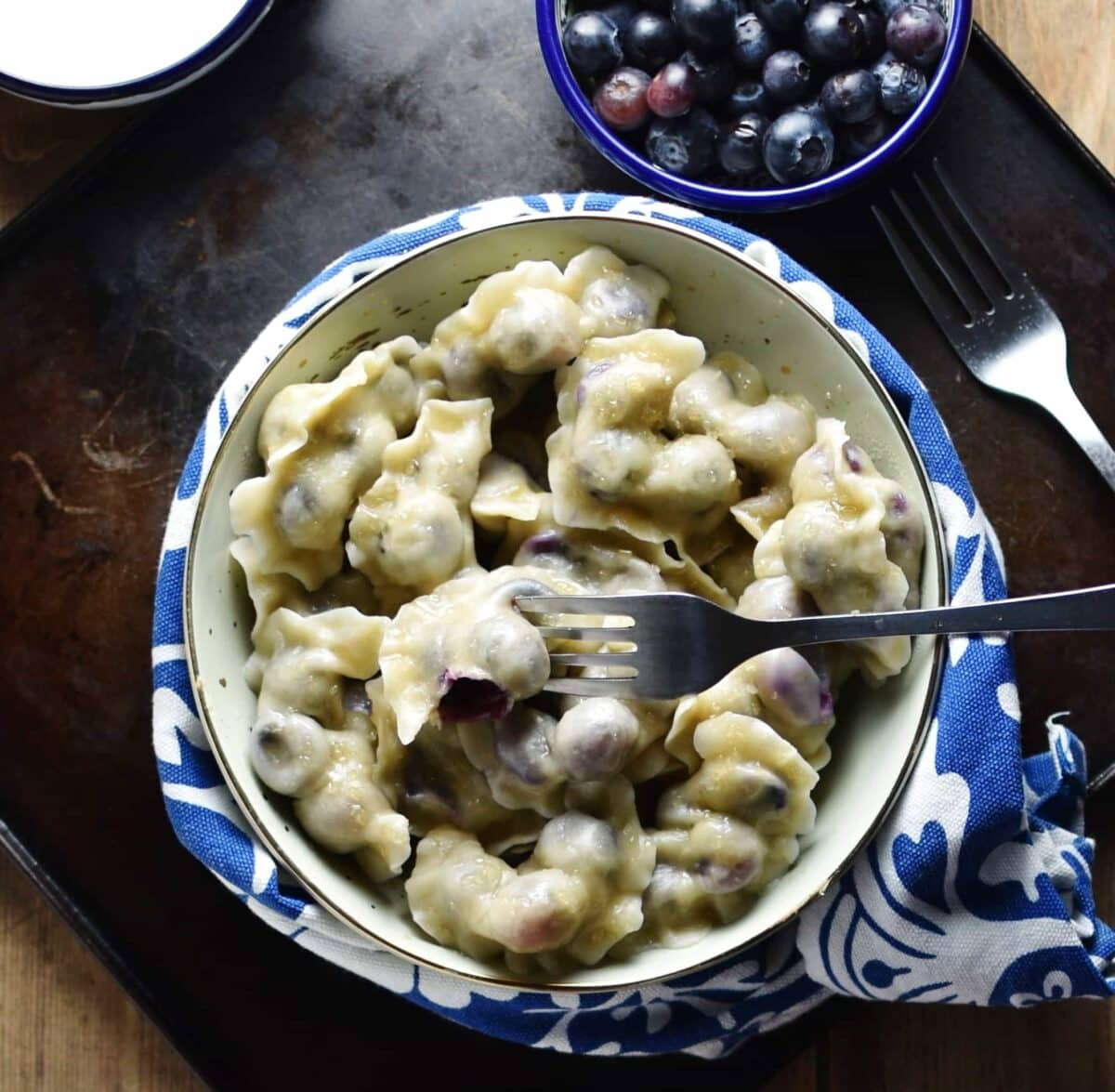 Top down view of blueberry pierogi with fork inside yellow bowl wrapped in blue-and-white cloth, with fork, blueberries in blue dish and yogurt in another dish.