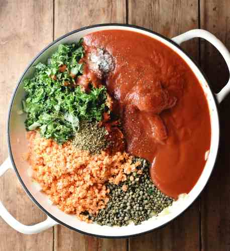 Top down view of lentils, kale and tomato sauce in large white dish.