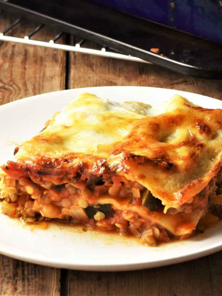 Side view of lentil lasagne slice on top of plate.