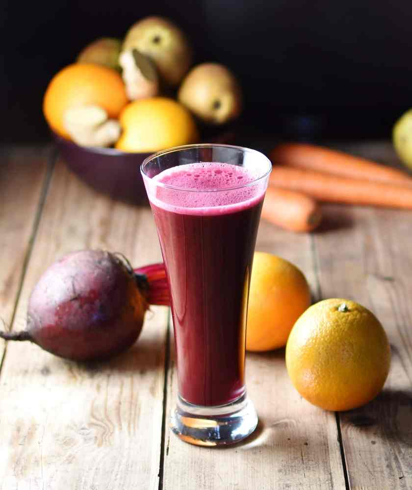Side view of red cabbage juice in tall glass with 2 oranges, beet and other fruits and vegetables in background.