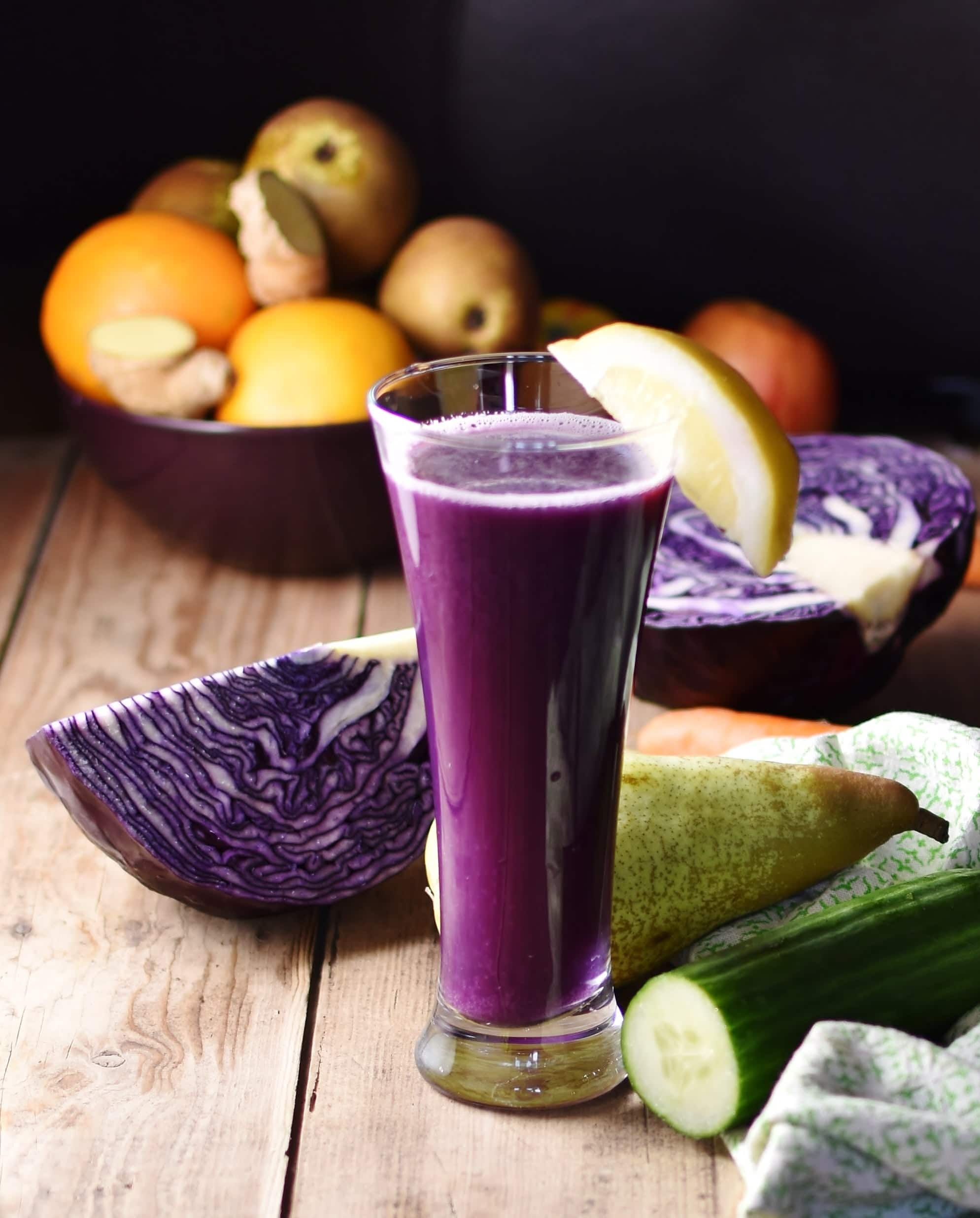 Side view of red cabbage juice inside tall glass with lemon wedge, with red cabbage, pear and cucumber on top of green cloth and more vegetables and fruits in background.