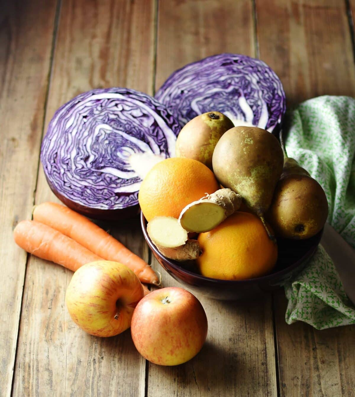 Raw apples, carrots and halved red cabbage on top of wooden surface with pears, oranges and ginger inside purple bowl and green cloth to the right.