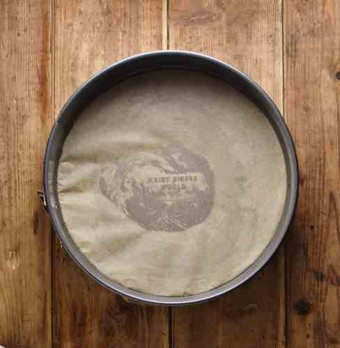 Top down view of round cake pan with parchment paper at the bottom.