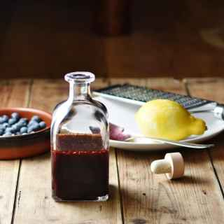 Blueberry dressing in bottle, with blueberries in brown dish, lemon, zester and spoon on top of white plate and bottle top in background.