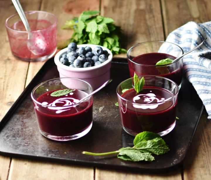 Side view of fruit soup in 3 glasses with fresh mint and blueberries in pink cup on top of tray,with mint, blue cloth and dish with spoon in background.