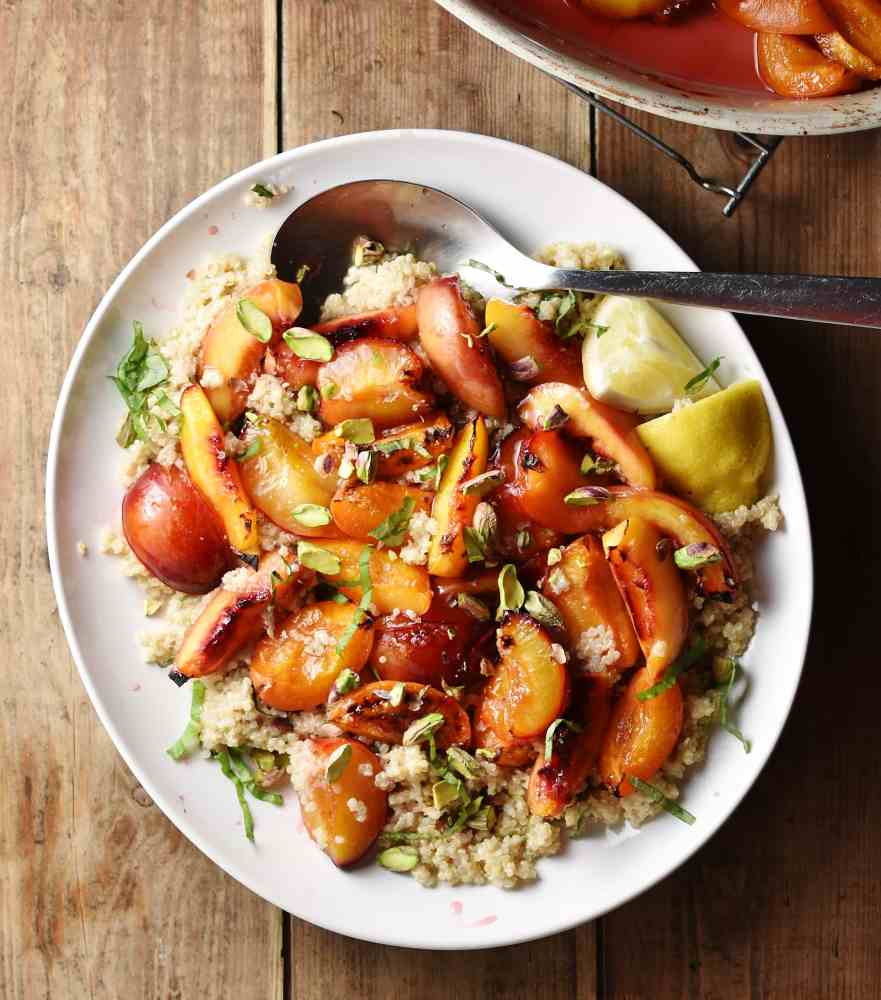 Quinoa salad with peaches, lemon wedges and nuts on top of white plate with large spoon.