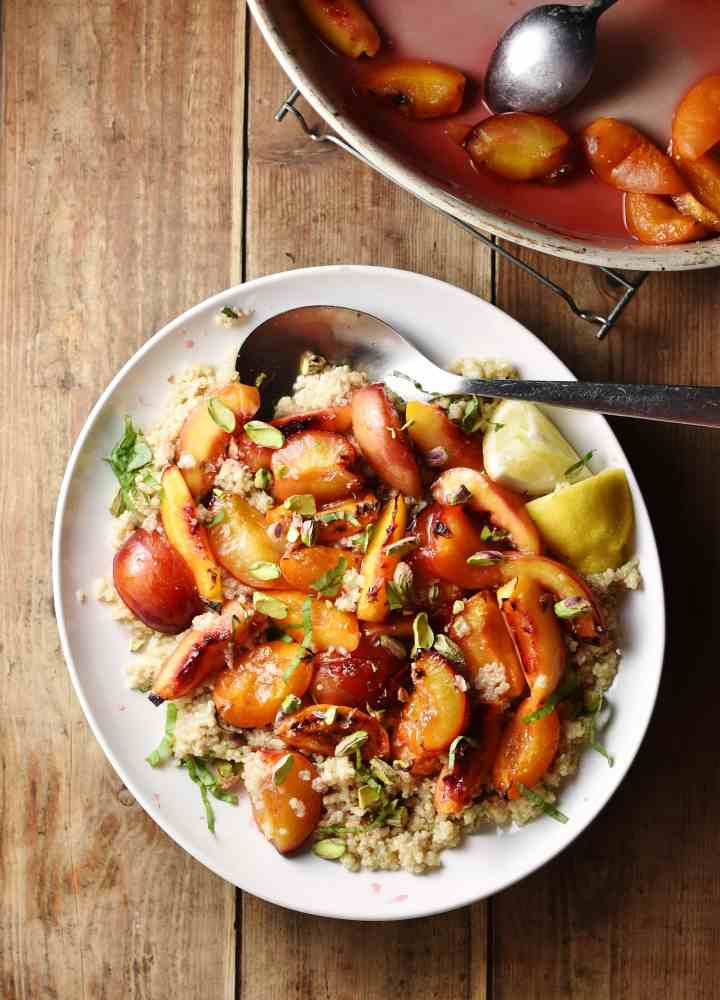 Roasted peach wedges with nuts and herbs on top of quinoa, with lemon wedges and spoon on white plate, with cooked peaches and syrup inside oven dish in top right corner.