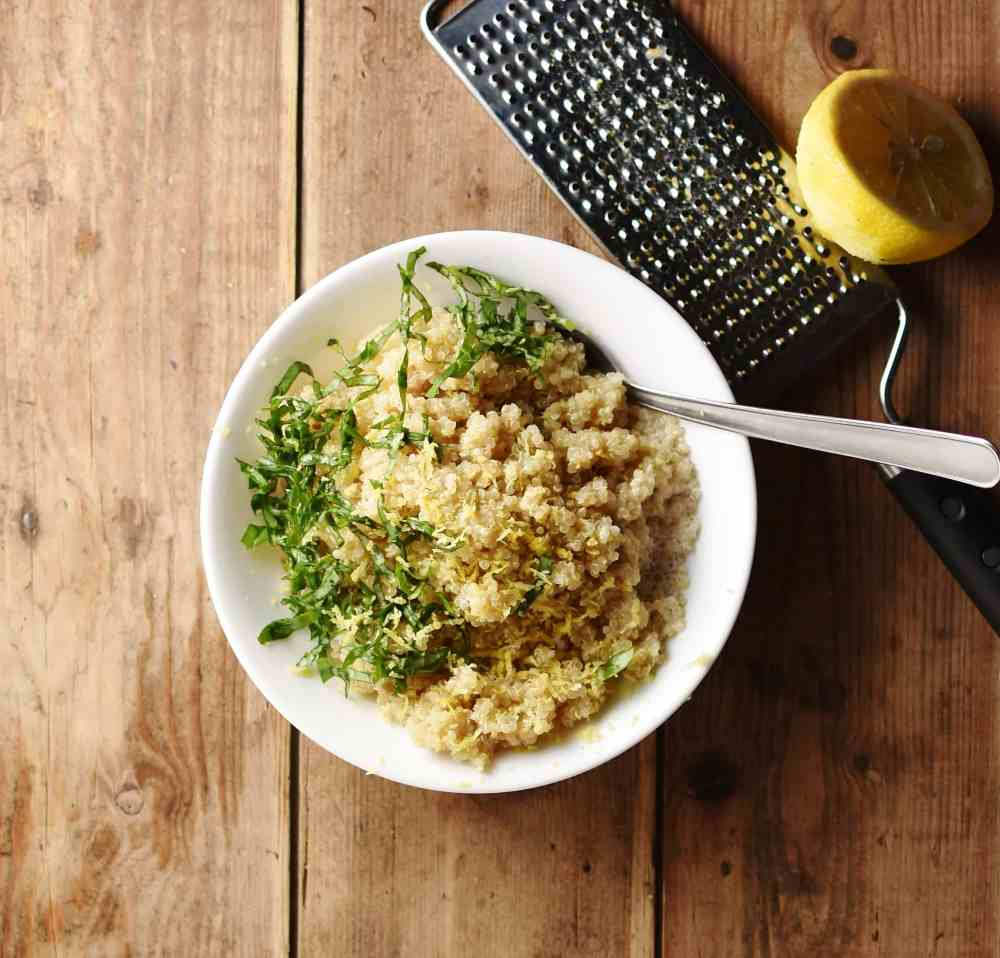 Cooked quinoa with chopped herbs and spoon inside white bowl, with lemon half on top of zester in background.
