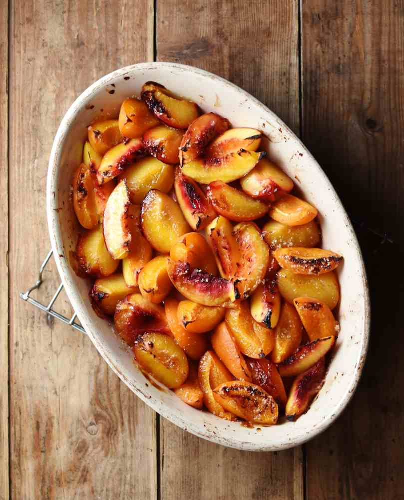 Top down view of roasted peach wedges inside white oval dish.