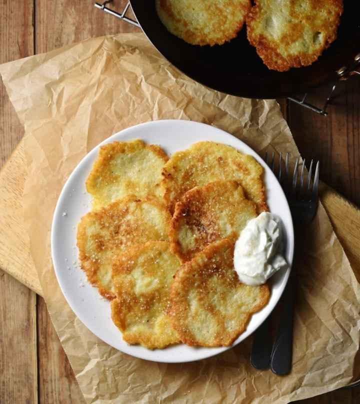 Crispy Polish potato pancakes with yogurt on white plate on top of paper, with pancakes in pan in top right corner.