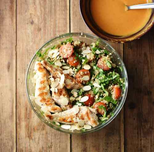 Quinoa, spinach, grilled chicken, cherry tomatoes and almond flakes in large bowl, with orange coloured dressing in another bowl in top right.