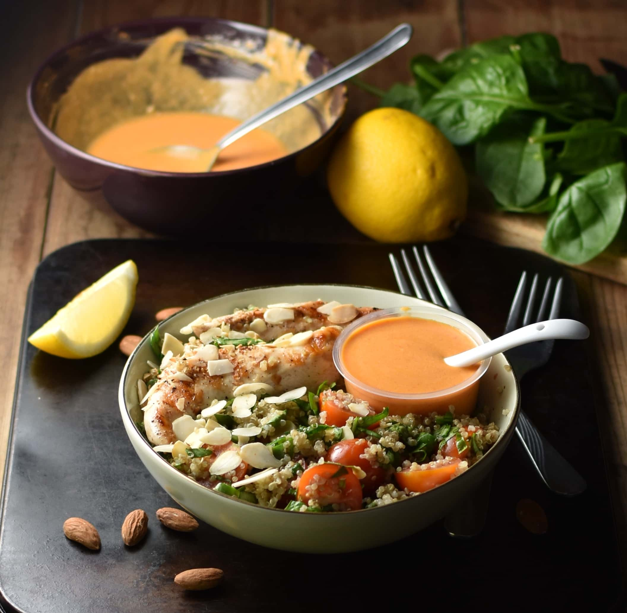 Side view of quinoa, chicken, spinach, tomato salad in green bowl with orange coloured dressing in small dish and white spoon inside, with 2 forks, lemon dressing in purple bowl and spinach in background.