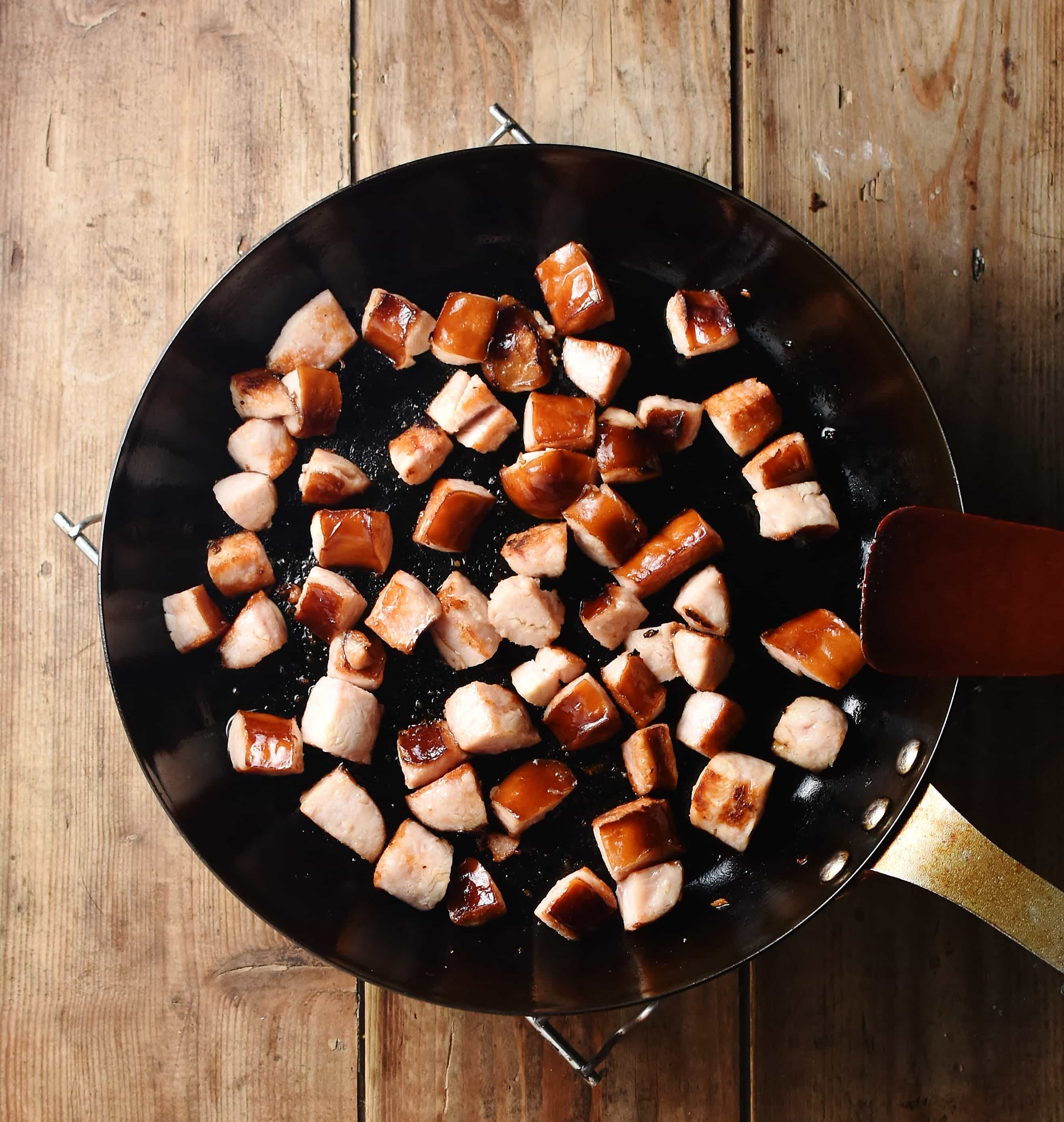 Chopped sausage frying in large pan.