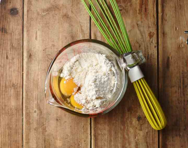 2 eggs and flour in jug with spout and green whisk to the right.