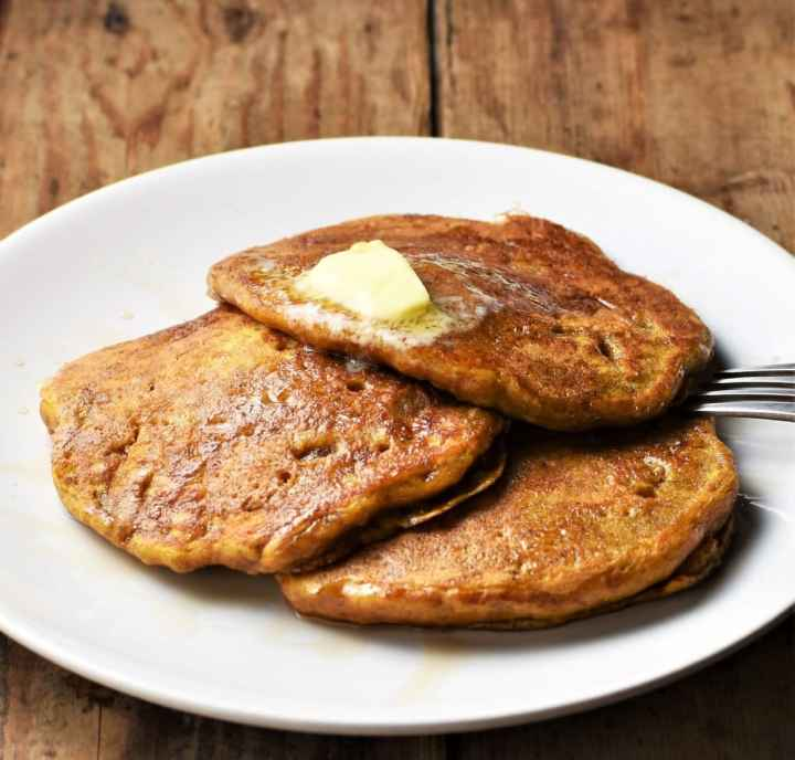 Side view of 3 pancakes with butter on white plate.