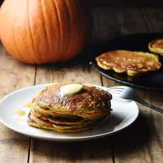 Pumpkin pancakes with knob of butter on top stacked on white plate, with fork, pancakes in pan and large pumpkin in background.
