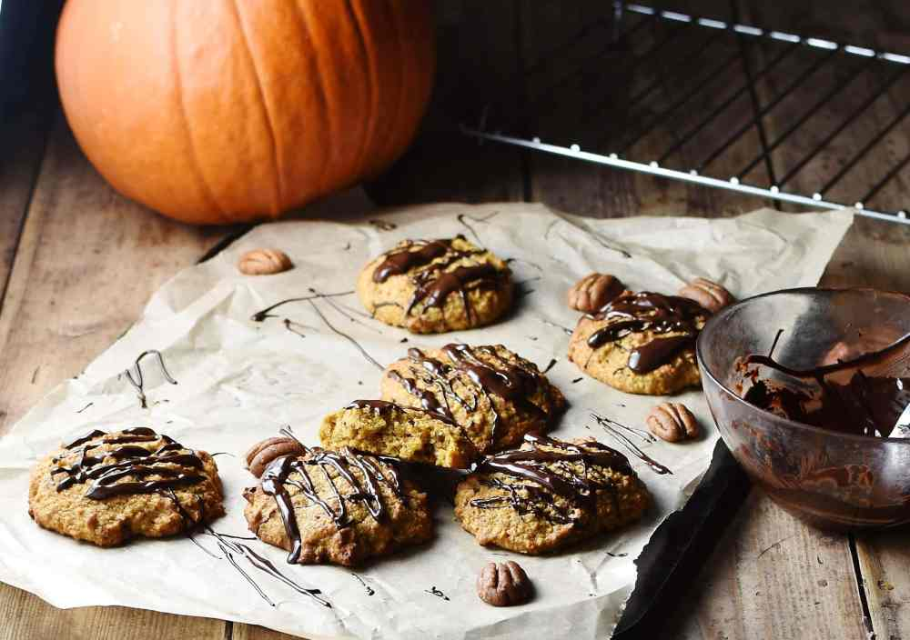 Cookies with chocolate drizzle on paper with pecan nuts, and pumpkin in background.
