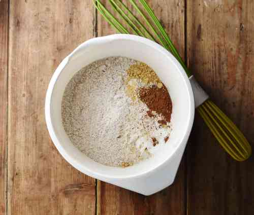 Flour and spice mixture in large white bowl with green whisk in background.