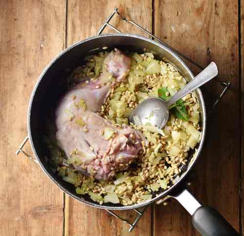 Top down view of chopped onions and barley with chicken leg and spoon in large pot.