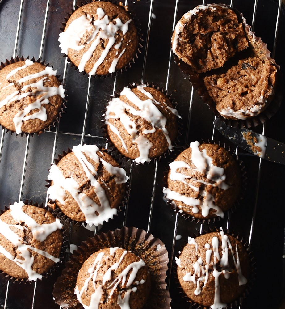 Gingerbread muffins with icing on top of rack.