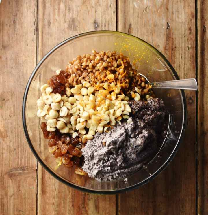 Kutia ingredients including wheat berries, creamy poppy seed mixture, raisins and nuts in mixing bowl with spoon.